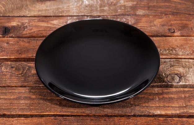 Pusty czarny talerz na drewnianym stole
