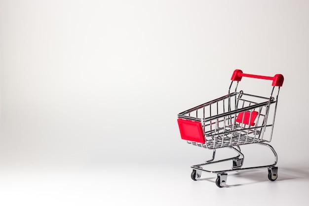 Pusty czerwony koszyk z supermarketu na białym tle na notatki lub tekst