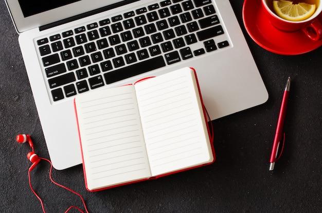 Pusty czerwony notatnik, laptop komputerowy, słuchawki i filiżanka herbaty.