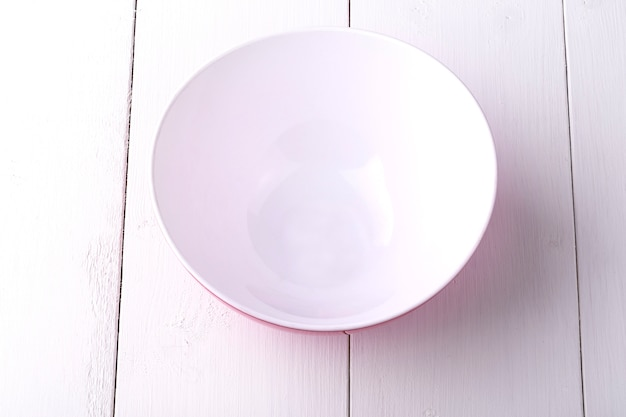 Pusty czerwony sałatkowy puchar na białym drewnianym stole