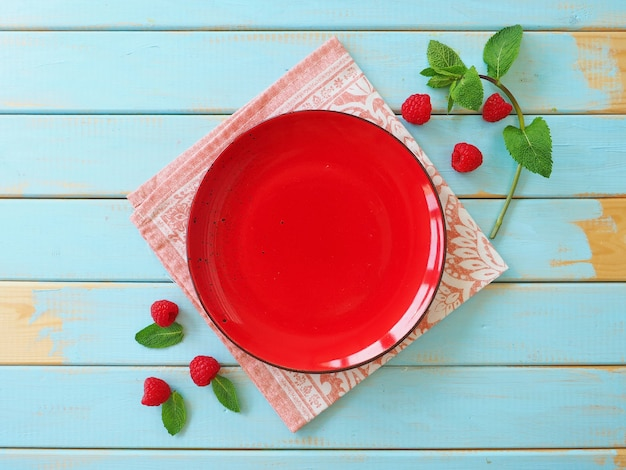 Pusty czerwony talerz malin i liści mięty na niebieskiej powierzchni drewnianych