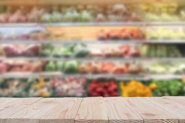 Pusty drewnianej deski stołowy wierzchołek na zamazanym supermarketa tle. skopiuj miejsce
