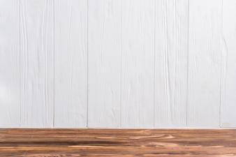 Pusty drewniany biurko przeciw biel malującej ścianie
