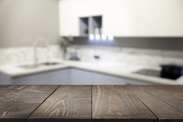 Pusty drewniany blat i niewyraźna nowoczesna kuchnia jako tło dla projektu