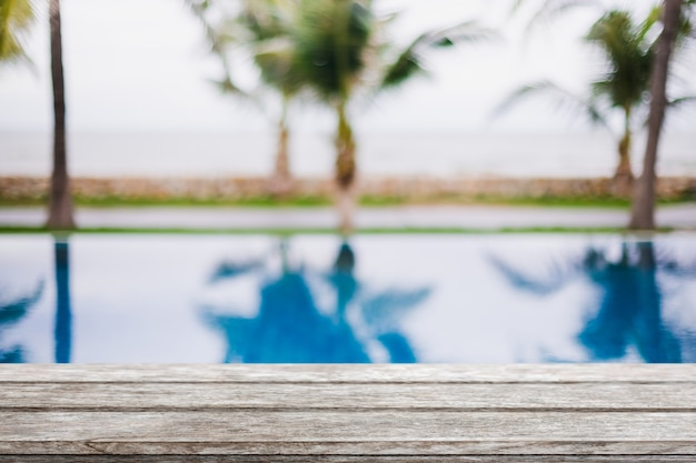 Pusty drewniany blat i niewyraźne basen w tropikalnym kurorcie latem