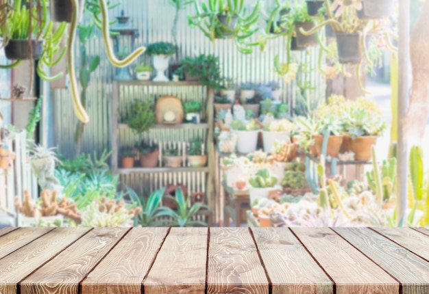 Pusty drewniany blat i niewyraźny zielony dom z kaktusem i soczystym
