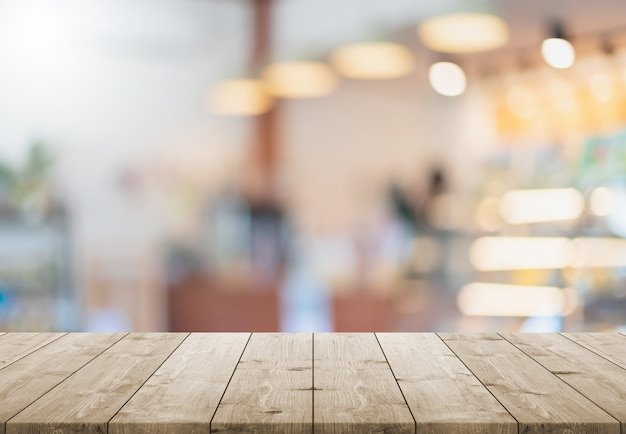 Pusty drewniany blat i rozmycie szklane okno wnętrza restauracji i kawiarni
