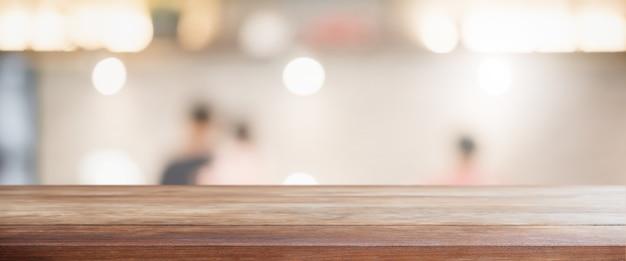 Pusty drewniany blat i rozmycie szklanego okna wnętrza restauracji