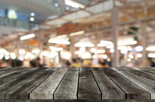 Pusty drewniany blat lub drewniany taras z rozmytym światłem