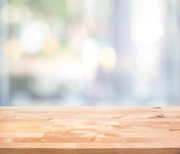 Pusty drewniany blat na rozmycie abstrakcyjnego widoku szyby. do montażu ekspozycji produktu lub projektowania kluczowego układu wizualnego
