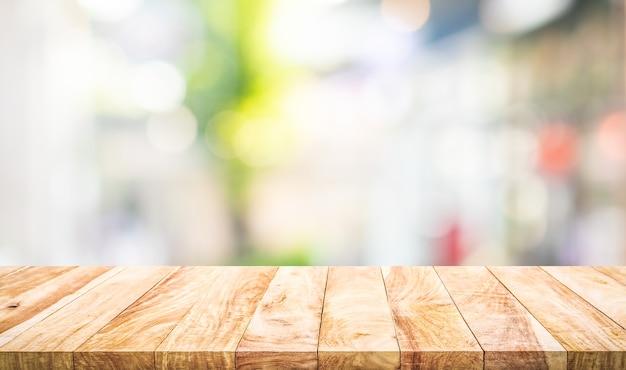 Pusty drewniany blat na rozmycie abstrakcyjnego widoku szyby. do montażu ekspozycji produktu lub projektowania kluczowych układów wizualnych