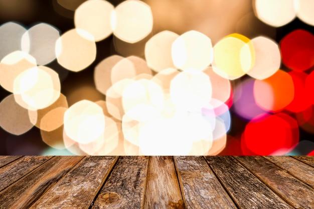 Pusty drewniany blat z abstrakcyjnymi rozmytymi wielobarwnymi, różowymi, czerwonymi, białymi, żółtymi, niebieskimi, nakrapianymi bokeh rozmytymi światłami tła miasta