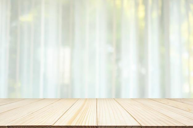 Pusty drewniany blat z rozmazanym białym oknem kurtynowym i zielonym tłem ogrodowym dla szablonu wyświetlania produktu