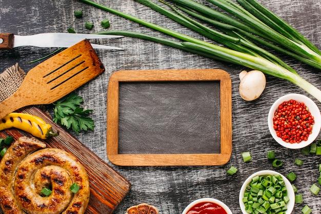 Pusty drewniany łupek otoczony grillowanymi kiełbaskami i świeżym składnikiem
