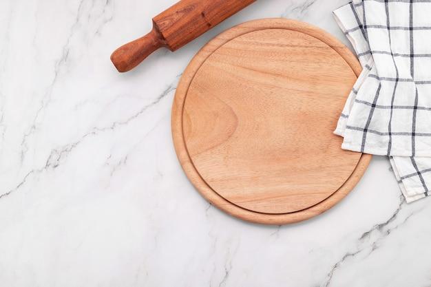 Pusty drewniany półmisek do pizzy z serwetką i wałkiem do ciasta na marmurowym stole kuchennym. deska do pizzy i obrus na białym tle marmuru.