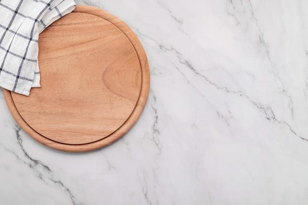 Pusty drewniany półmisek do pizzy z serwetką na marmurowym stole kuchennym z kamienia. deska do pizzy i obrus na białym tle marmuru.