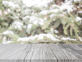 Pusty drewniany stół przed choinką z śniegiem