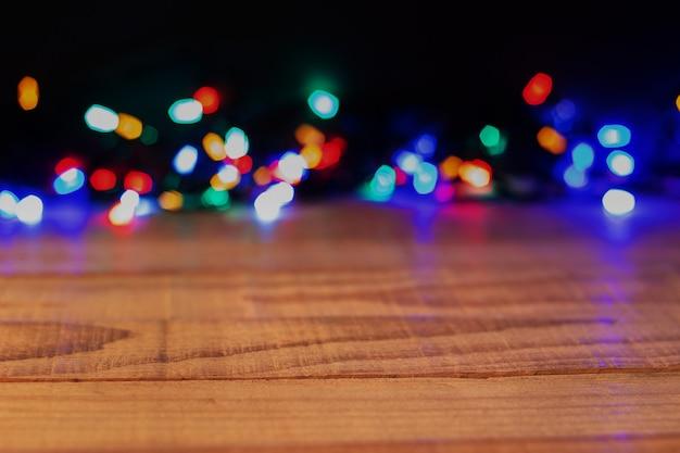 Pusty drewniany stół i kolorowe świąteczne światła, kopia przestrzeń. efekt bokeh