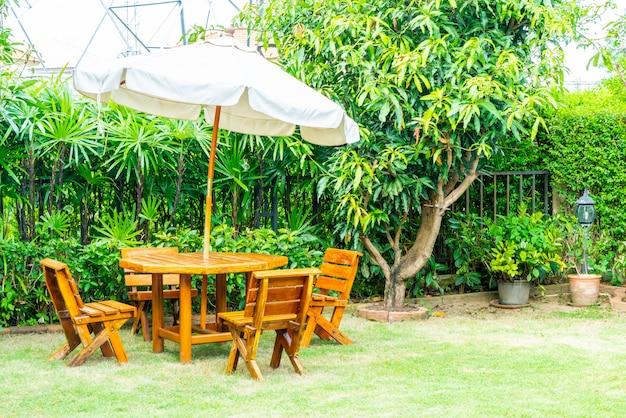 Pusty drewniany stół i krzesło ogrodowe w ogrodzie domu