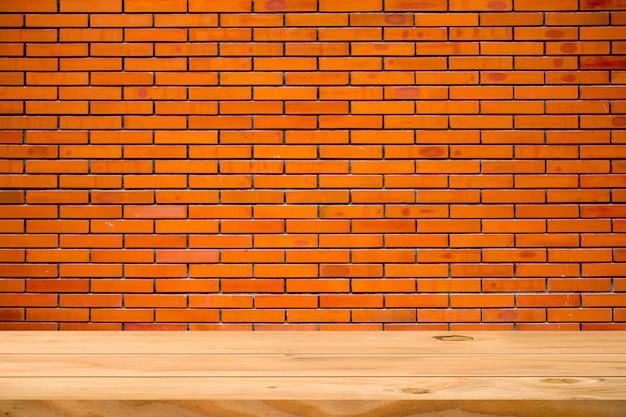 Pusty drewniany stół i mur z cegły. gotowy do montażu produktu.