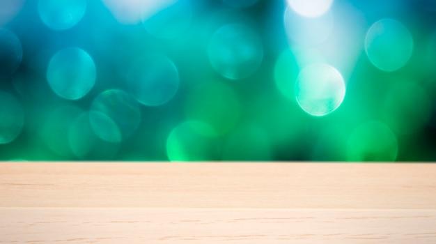 Pusty drewniany stół i rozmyte bożonarodzeniowe lampki w tle