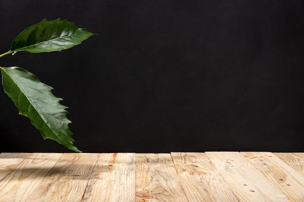 Pusty drewniany stół i zielone liście na czarnej ścianie