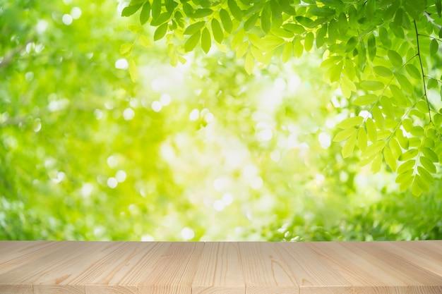 Pusty drewniany stół na zielonym natury tle z piękna bokeh pod światłem słonecznym.
