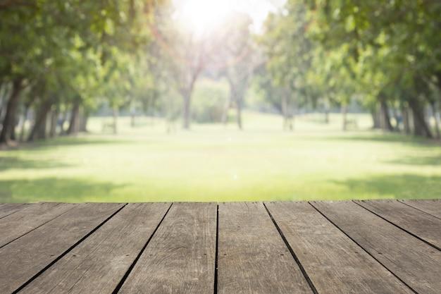 Pusty drewniany stół / podłoga parka plamy tło publicznie z zielonymi drzewami