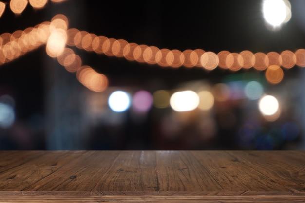 Pusty drewniany stół przed abstrakcyjnym niewyraźnym światłem nocnym