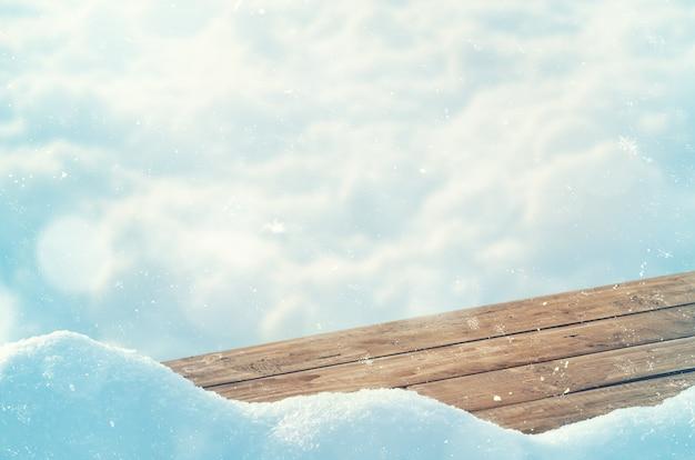 Pusty drewniany stół przed rozmytym tłem z płatkami śniegu