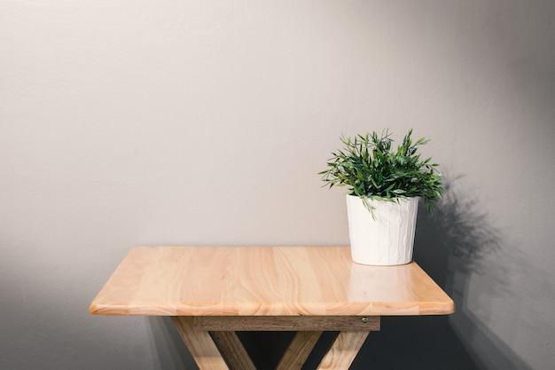 Pusty drewniany stół z rośliną doniczkową na szarym tle
