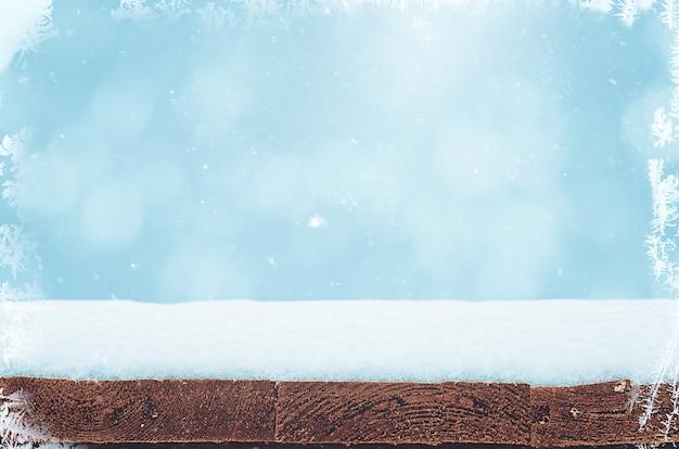Pusty drewniany stół z warstwą śniegu przed rozmytym tłem z płatkami śniegu