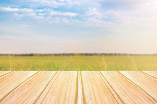 Pusty drewniany stół z zamazanym zieleni polem na tle i niebieskim niebie