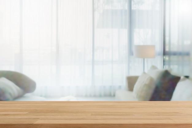 Pusty drewniany stołowy wierzchołek i zamazany domowy wnętrze z zasłony okno tłem. - może służyć do wyświetlania lub montażu produktów.