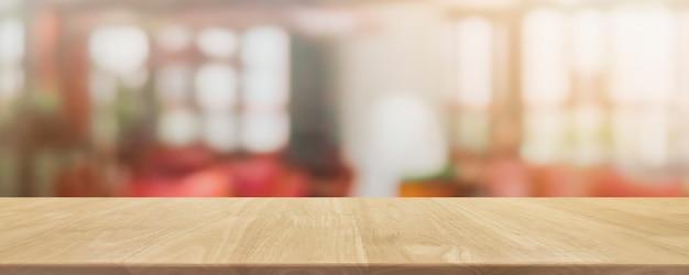 Pusty drewniany stołowy wierzchołek i zamazany tło sklep z kawą i restauracją.