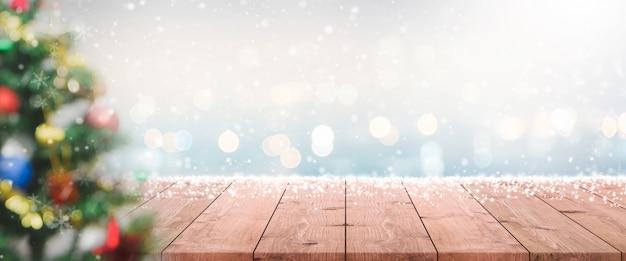 Pusty drewniany stołowy wierzchołek na plamie z bokeh choinki sztandaru tłem z opadem śniegu.
