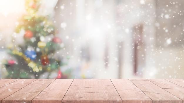 Pusty drewniany stołowy wierzchołek na plamie z bokeh choinki tłem z opadem śniegu.