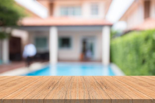 Pusty drewniany stołowy wierzchołek na zamazanym tle przy pływackim basenem w ogródzie