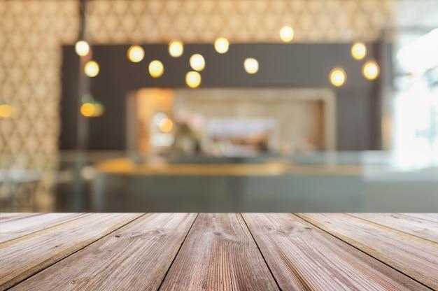 Pusty drewniany stołowy wierzchołek z zamazanym sklep z kawą wnętrza tłem.
