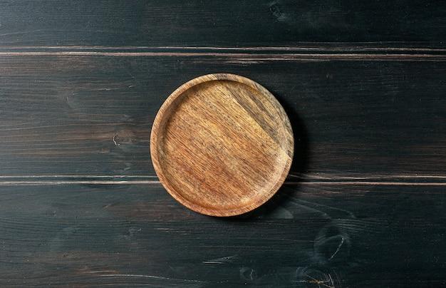 Pusty drewniany talerz na ciemnym stole w kuchni, widok z góry