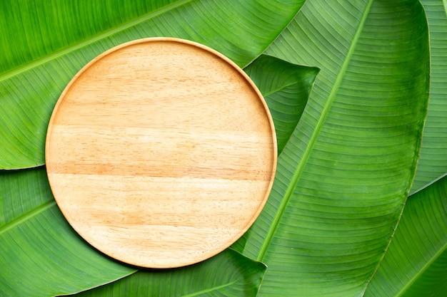 Pusty drewniany talerz na tle liści bananowca. widok z góry