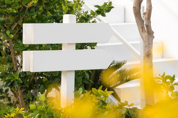 Pusty drewniany znak z dwa strzała w ogródzie
