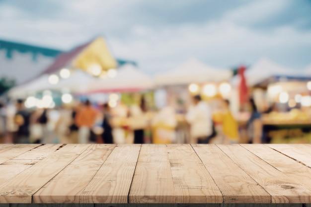 Pusty drewno stół i rocznika brzmienie zamazywali defocused tłumów ludzie w chodzącym ulicznym festiwalu i zakupy centrum handlowym.