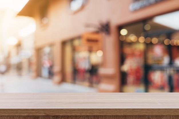 Pusty drewno stół i rocznika brzmienie zamazywaliśmy defocused tłumów ludzie w chodzącym ulicznym festiwalu i zakupy centrum handlowym.