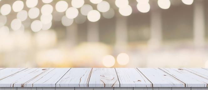 Pusty drewno stół i zamazany światło stół w zakupy centrum handlowym z bokeh tłem. szablon wyświetlania produktu.