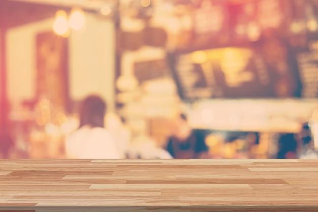 Pusty drewno stół i zamazany tło pokaz przy sklep z kawą z przestrzenią dla produktu.