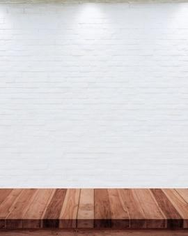 Pusty drewno stół z białym ściana z cegieł tłem.