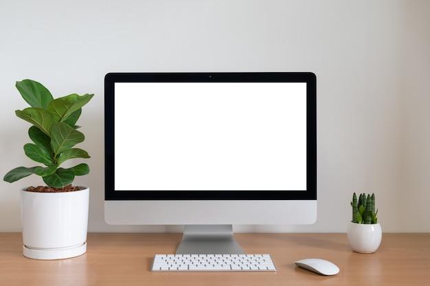 Pusty ekran komputera all in one z fiddle fig i sansevieria cylindrica plants na stole