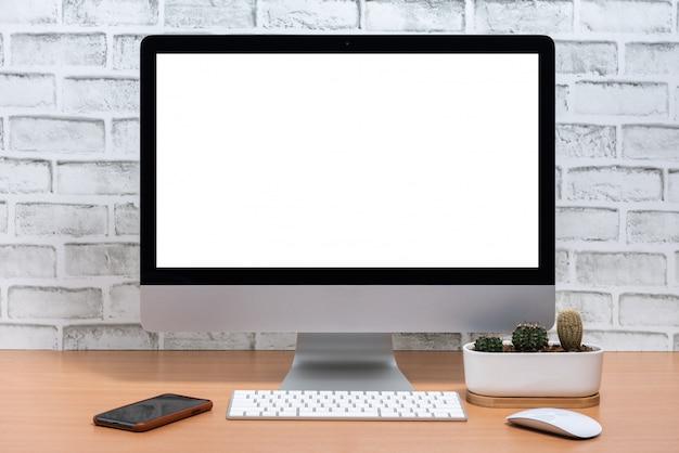 Pusty ekran komputera all in one z inteligentnym telefonem i doniczką kaktusową na drewnianym stole