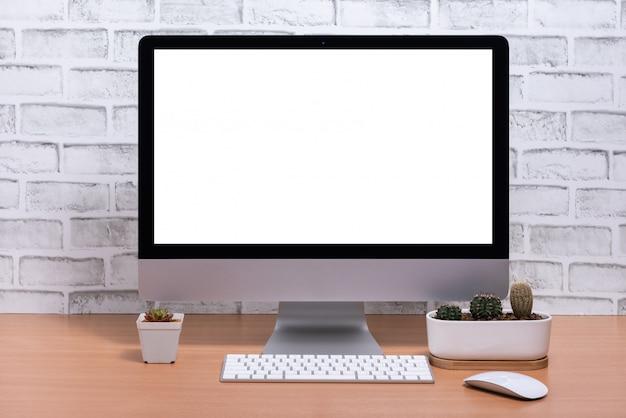 Pusty ekran komputera wszystko w jednym z doniczkami kaktusa na drewnianym stole